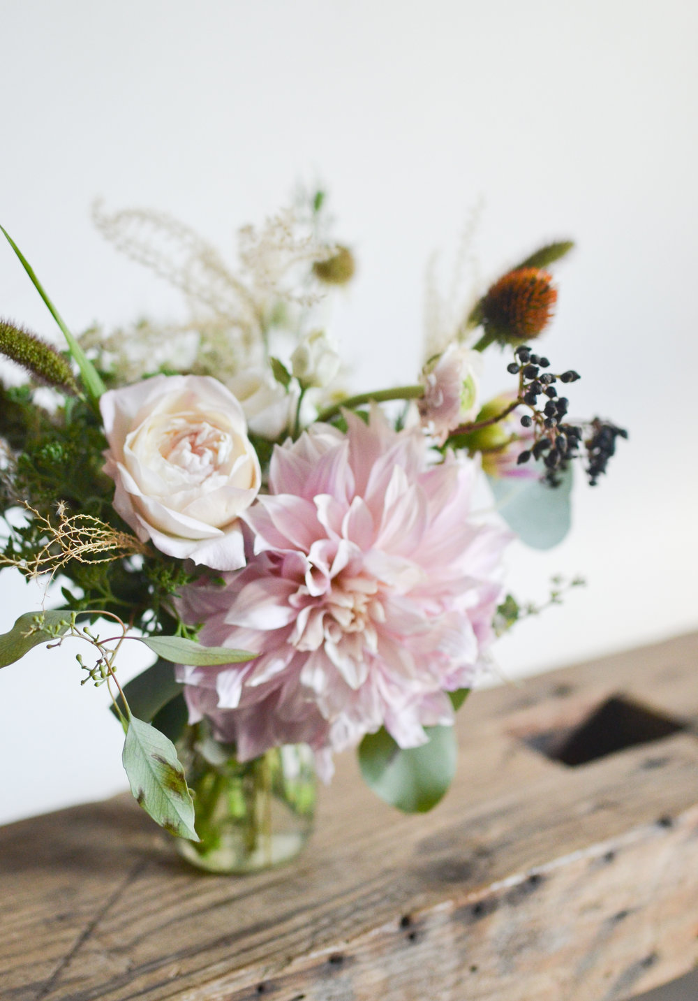 A high end centerpiece with dahlias, roses, ranunculus buds, and echinacea