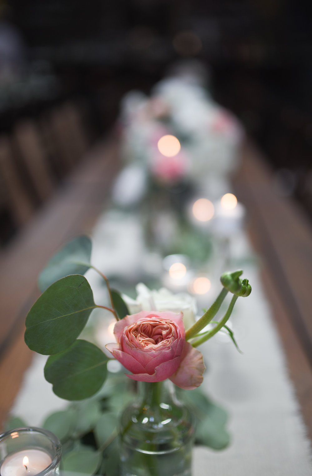 Pink garden roses are a show stopper in bud vases at the Brooklyn wedding