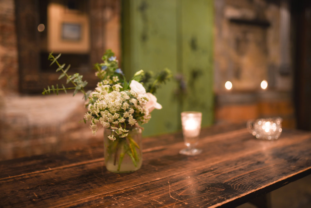 Flower arrangements in mason jars at this Brooklyn wedding reception