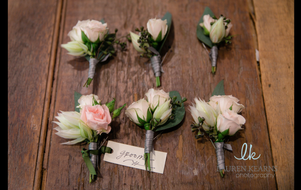 A thin ribbon wrap gives the boutonnieres texture
