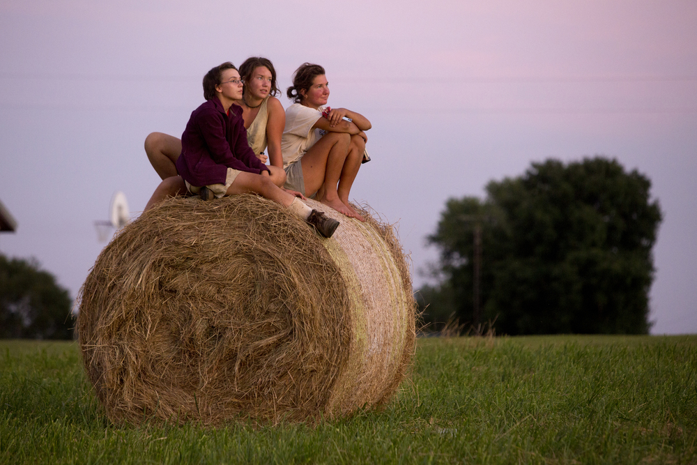 Living Roots Ecovillage farm apprentices Emily Spatt of Fort Wayne, left, Mecie Delffs of Grant Rapids, Mich., and Emily MacGibeny of New London, Conn. soak in the last rays of light across the street from the ecovillage in French Lick, Ind. on July 24, 2015.