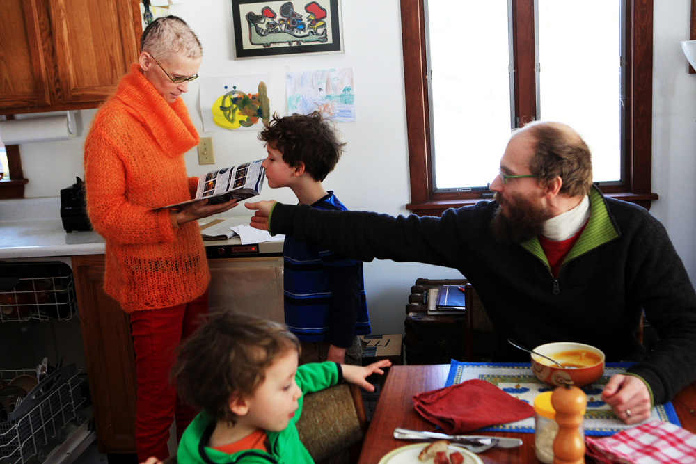 Sarah Thompson looks through a magazine as her son Wallace, 7, peeks over the top while her husband John and their other son Lysander, 4, ate lunch at their home in Georgetown, Maine on February 28, 2014.  Sarah, who is originally from Concord, was diagnosed with leukemia in 2010, then was in remission and feeling hopeful, and now needs a bone marrow transplant. NH Technical Institute will hold a marrow drive as part of its Wellness Fair on April 1.