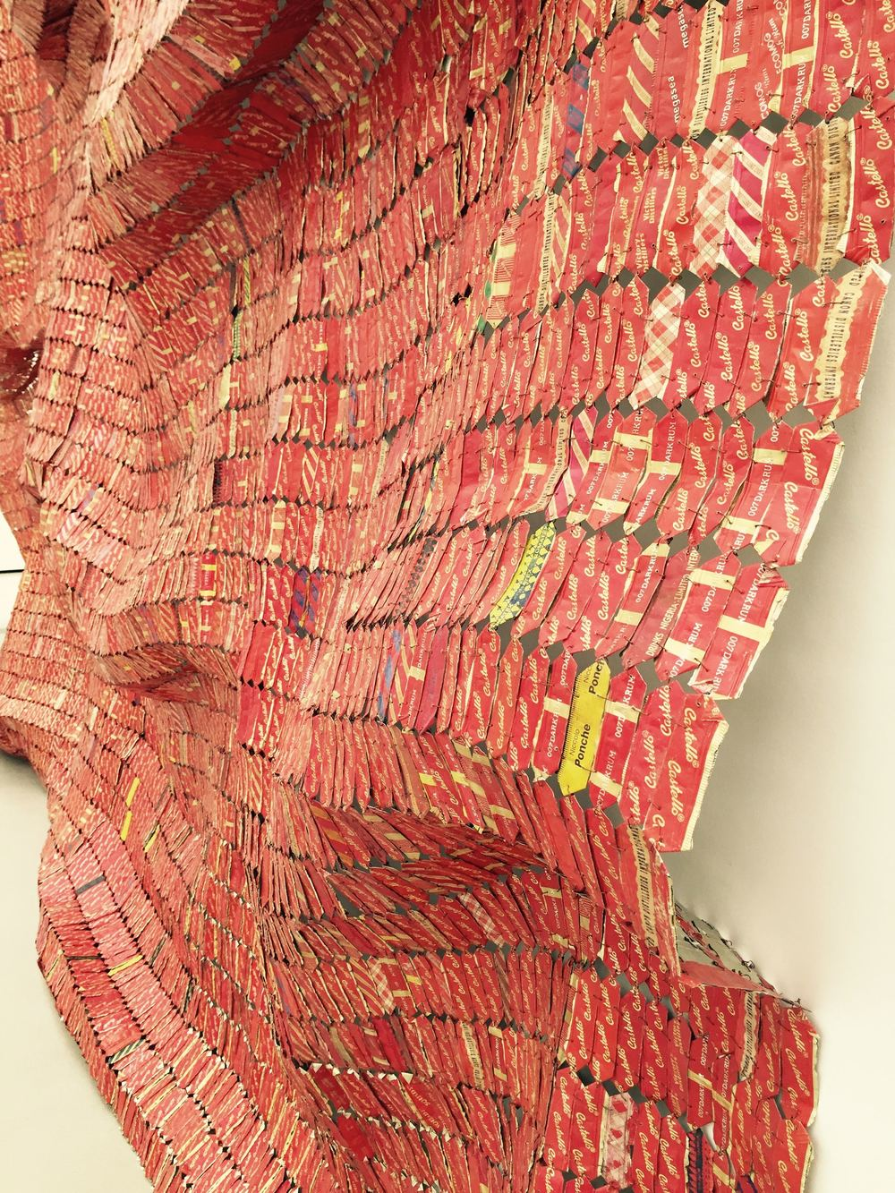 "[detail] ""Red Block"" by El Anatsui. Made from woven red liquor labels, the piece can be folded/bent according to the space in which its hung."