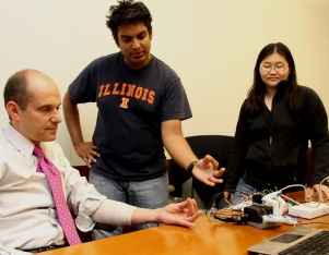 Aadeel Akhtar and Mary Nguyen teach US Embassador to Ecuador, Adam Namm, how to use their 3D-printed prosthetic hand.