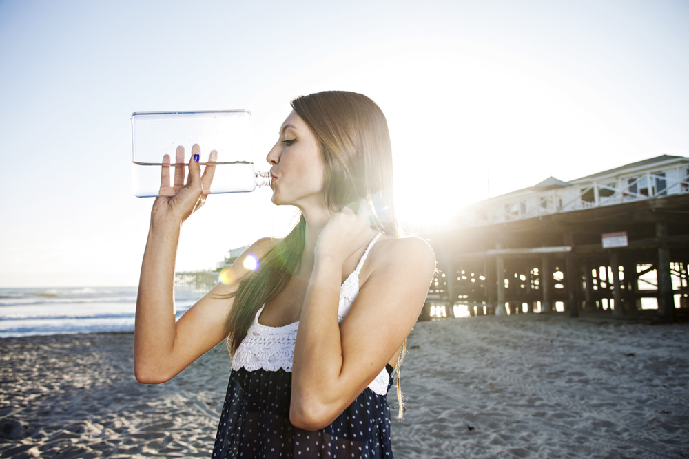 Cute girl drinking water at the beach. San Diego lifestyle, product and advertising photographer Jason Ward Studios.