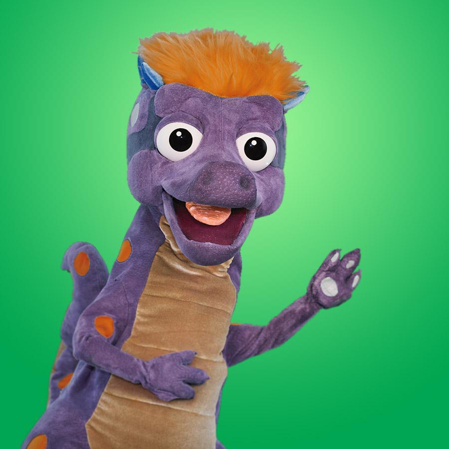 DINO   Dino es extinción con actitud. ¡Es muy inteligente y pícaro, y le gusta pavonearse! Siempre sabe bien qué es qué, y el mejor mejor camino para poder llegar.