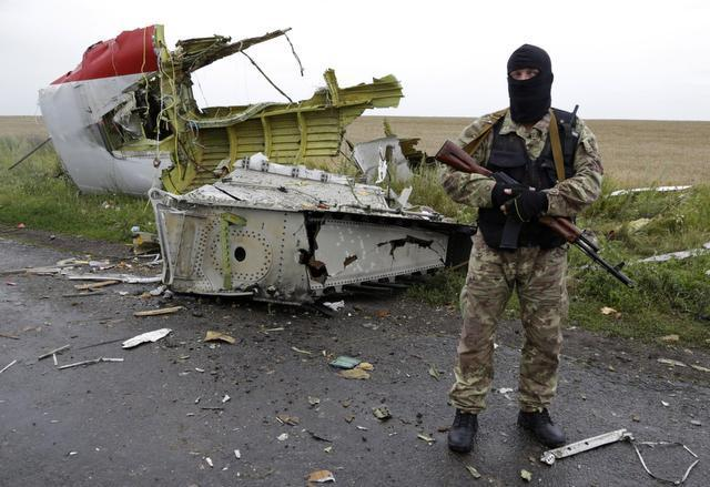 Dmitry Lovetsky/ The Associated Press  A pro-Russian fighter stands guard Friday at the site of a crashed Malaysia Airlines passenger jet near the village of Hrabove in eastern Ukraine.