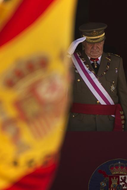 Andres Kudacki/The Associated Press King Juan Carlos salutes during a ceremony in Spain last week. His prestige stopped a military coup in the 1980s. Now he's stepping down and Prince Felipe will assume the throne.