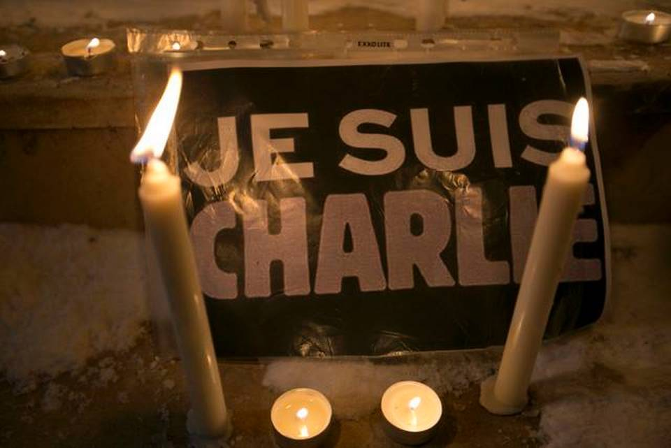 "Candles are lit near a sign that read in French ""I am Charlie"" lights a candle during a demonstration in solidarity with those killed in an attack at the Paris offices of the weekly newspaper Charlie Hebdo in the Kosovo capital Pristina on Wednesday.     Visar Kryeziu   Associated Press"