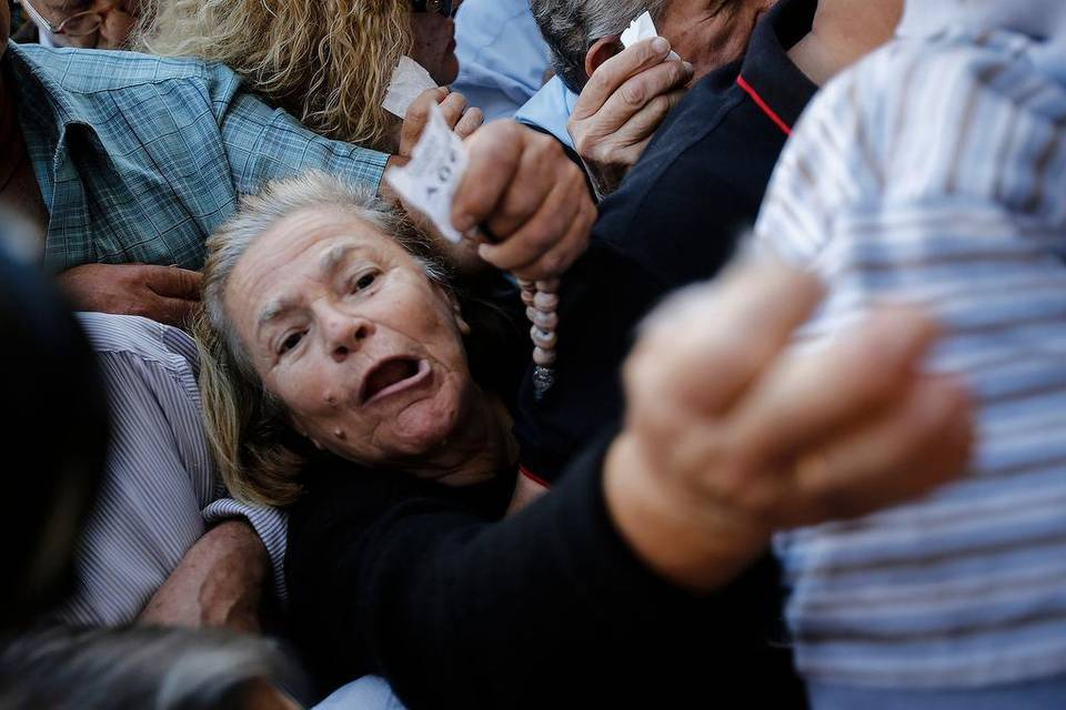 Pensioners wave ticket numbers as they try to get inside a National Bank of Greece branch in Athens last week. Elderly pensioners were stuck without monthly stipends as Greece deals with its financial crisis. | Simon Dawson Bloomberg News