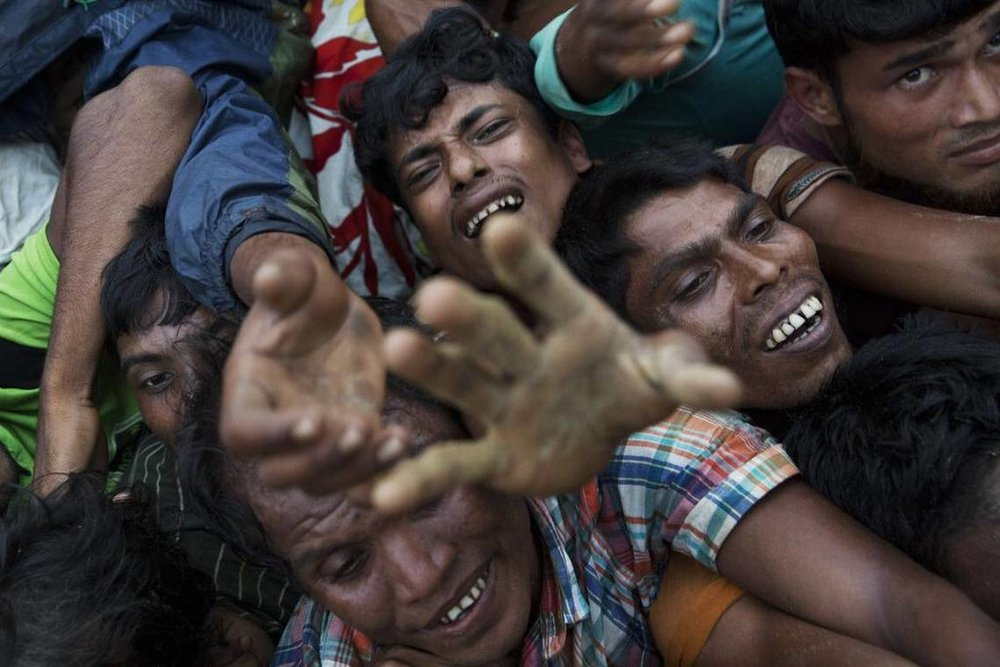 Rohingya Muslims stretch out their arms to reach food being distributed near Balukhali refugee camp in Cox's Bazar, Bangladesh, Wednesday, Sept. 20, 2017. With Rohingya refugees still flooding across the border from Myanmar, those packed into camps and makeshift settlements in Bangladesh are desperate for scant basic resources and fights erupt over food and water. Bernat Armangue AP