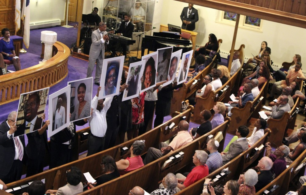 """Photos of the victims of the shooting at Emanuel AME Church in Charleston, S.C., are held during a vigil at the Metropolitan African Methodist Episcopal Church in Washington."" (AP/ Washington Post )"