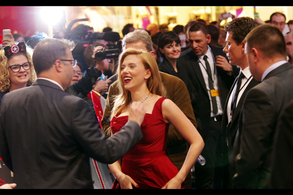 Somebody who appears to be Scarlett Johansson's bodyguard adjusts .... something. I'm not sure what, but if he's her bodyguard and he's behaving inappropriately the only person she can call to for aid IS her bodyguard. Or me - I'd be happy to help. I just need about five minutes notice so I can circumnavigate the waist of the photographer in the paparazzi pen in front of me.