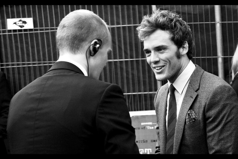 """Be honest, that's Justin Bieber coming from your earpiece, isn't it?""  Sam Claflin has arrived, and he's just taken the moral highground away from the security staff."