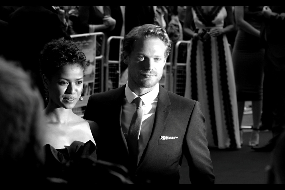Gugu Mbatha-Raw and Sam Reid pose. Sam Reid, incidentally, was in (and at the premieres of.. I think) both  Anonymous (2011)  and  The Railway Man (2013) . He's got a certain Tom Hardy vibe about him... insofar as he's wearing a suit, I suppose.