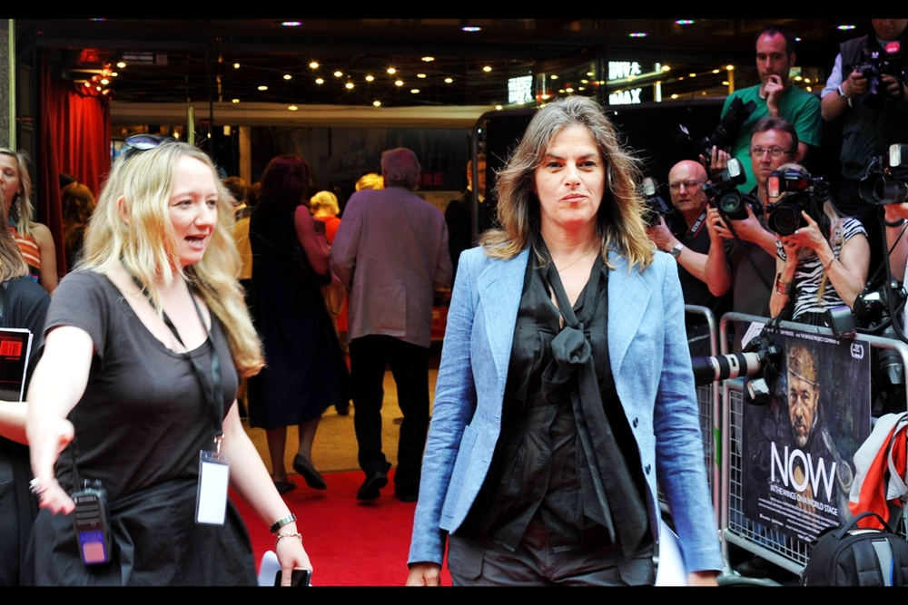 I think she's a singer and she's not affiliated with the film. So that should narrow it down... Edited to add : she's actually artist Tracey Emin, whose (unmade) work 'my bed' was shortlisted for the 1999 Turner prize and was bought by Charles Saatchi £150,000 and is currently on sale...