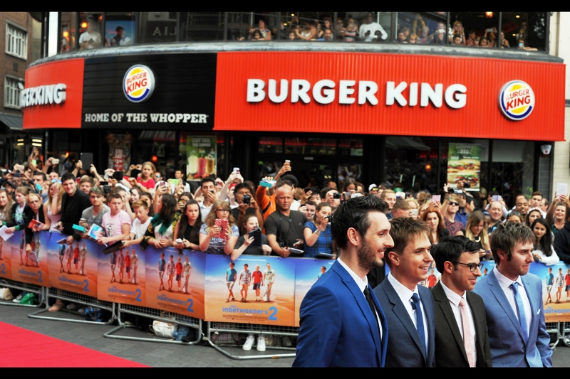 Excellently, the four arrange themselves in front of the VIP Paparazzi cordon in front of a duly designated Fast Food Restaurant Product Placement as the crowd screams their approval, calls for their autographs, and feel faint or dizzy or get the vapours or whatever teen girls do when they get in proximity to famous teenage guys.