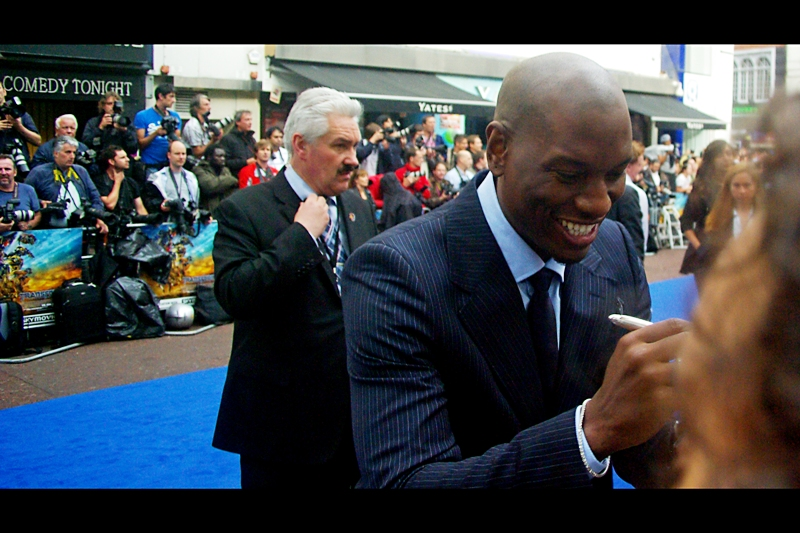 The Red (Blue) Carpet is far too packed to take photos of people getting out of cars or posing for the Paparazzi, and they haven''t yet begun to be interviewed where they'll be blocked by passersby and hovering attendants in orbit around them. Still... for now, this is Actor Tyrese Gibson (and behind him, the head of security at most of these premieres. Hmm.... perhaps I should pixelate him out of the picture to protect his identity?)