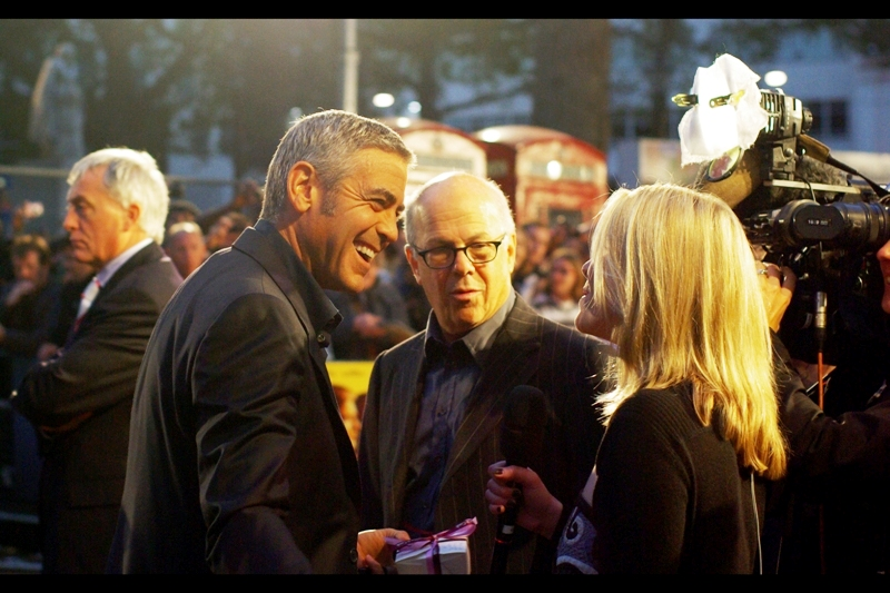 George Clooney may be sharing a laugh with a reporter, but I think the real story in this picture is the body language of the security dude in the background to the left...