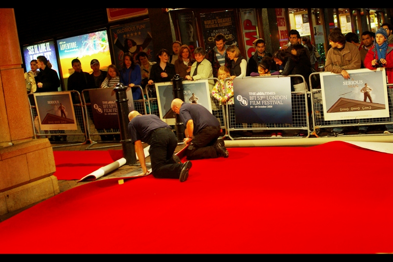A kinked Red Carpet means this is a smaller premiere. (From brutal experience, this typically means Charlize Theron will not attend, and even Yellow Cap Guy is only a 'maybe'). This movie was for a Coen Brothers film, so perhaps one or both would deign to attend. And John Hurt would probably show up regardless.