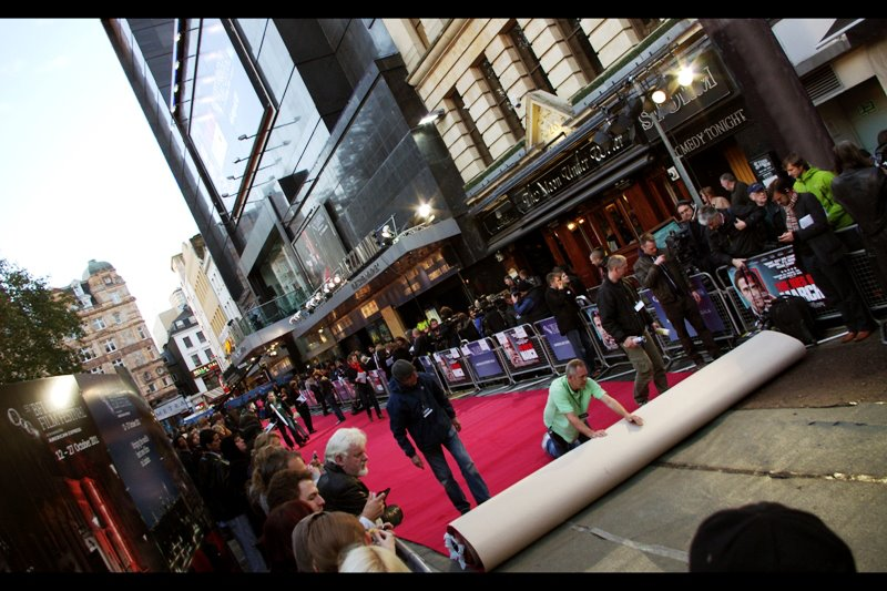 There are major refurbishment works in place for Leicester Square which meant that the construction works had to move their perimeter fencing back about a metre and a half AND fill open holes with tar and lay board just for the premiere before they could lay the red carpet. It's a 'behind-the-scenes' thing.