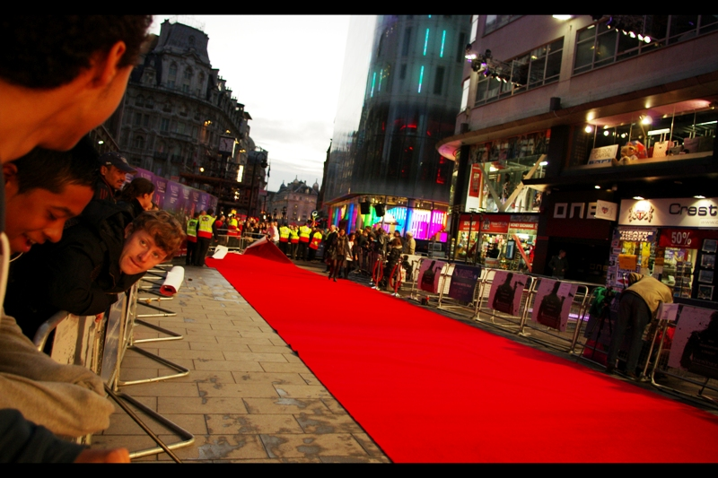 It had rained quite heavily before this premiere (I was having lunch where it was dry)...  but the carpet was laid and the crowd was out, and I was loving the possibility of interesting backlighting from the M&Ms store in the distance once the premiere got underway.