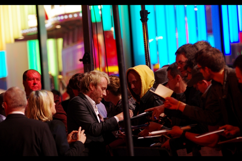 Actor Rhys Ifans signs for Awesomely Creepy Yellow Hooded Guy (no relation to the guy who used to wear the cap of the same colour). Meanwhile the colour of Tomato Red Security Guard Dude is provided courtesy of the fantastic lighting of the Leicester Square M&Ms Store