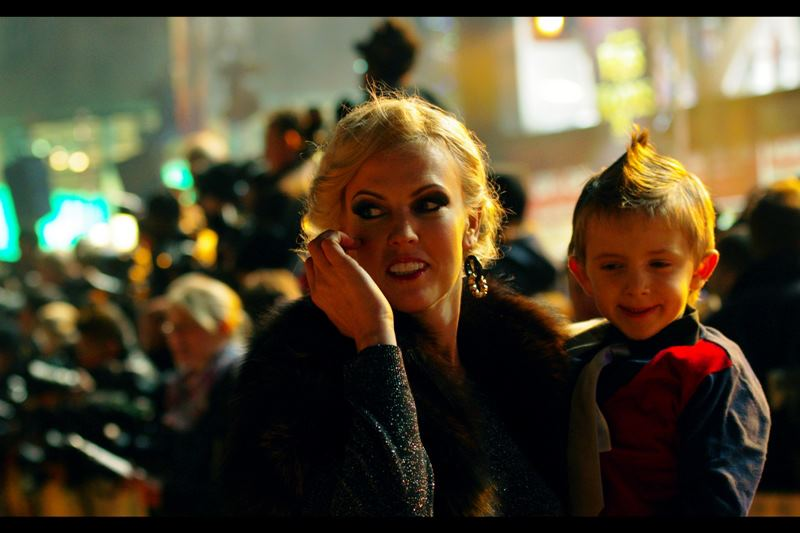 No idea who she is, but the Paparazzi were distracted by her, and/or her son's amazing hairstyle.