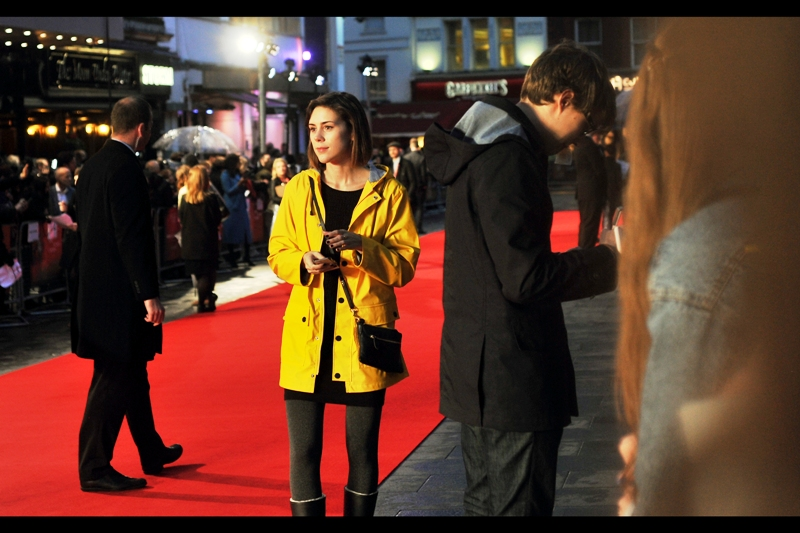 This is the girlfriend of the guy signing autographs to her left (Chris? Charles? David?). She seems like she'd rather be anywhere else. Her combination black dress / yellow raincoat seems to want to be in two different places at once.