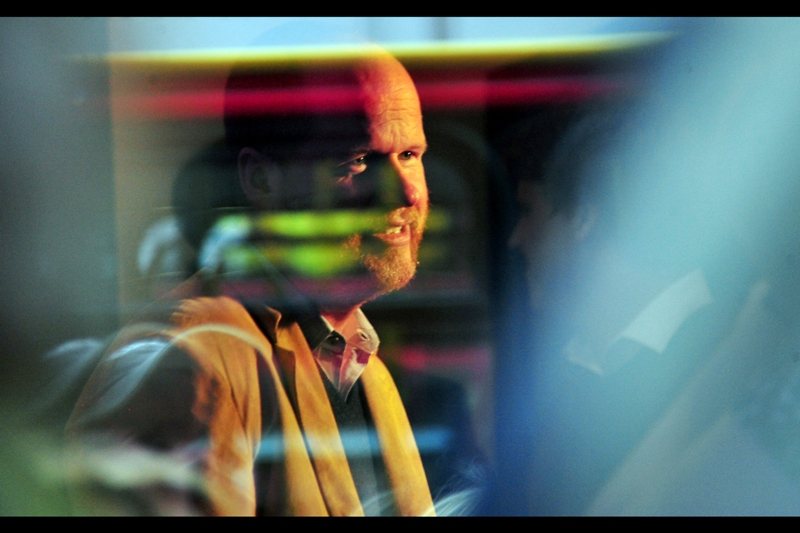 "Joss Whedon, reflected in a window... with the reflection of a bus reflected IN that window, along with the reflection of a man standing in front of him without a light source. There is almost no way you could *deliberately* set up this shot... but I'll take it. (Also falls under the category ""Blurry, therefore Art"")"