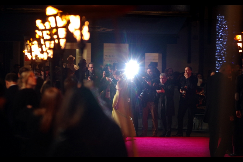 "The actress behind the yellow dress and lens flare is Jena Malone, and my Pentax starts giving evidence to the fact that it's going to be highly picky and choosy as to what its definition of ""centre focus"" is."