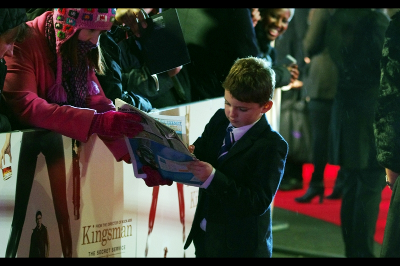 """Six Across? 'DIRIGIBLE', ma'am. Is this your first crossword?""  Wireimage identifies the kid as ""Alex Nikolov"", who plays 'Young Eggsy' in the film. And I'm not nearly tired enough to fail to consider that odd."