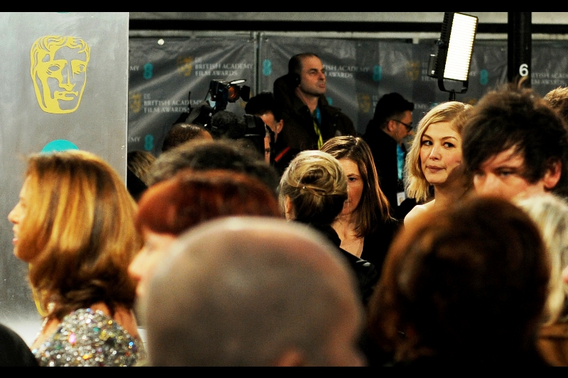 "Actress Rosamund Pike (""Gone Girl"") briefly emerges from behind the crush of the red carpet to look at a guy in the foreground whose head is a lot larger than perspective shift can quite explain."
