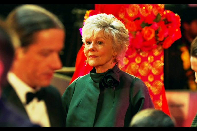 "Diana Hardcastle's green attire could best be described as 'severe' by people who are all ""wait... isn't this meant to be a Bollywood-themed film, and wasn't Dame Judi Dench wearing somthing you could camouflage her against a Persian Rug?"""