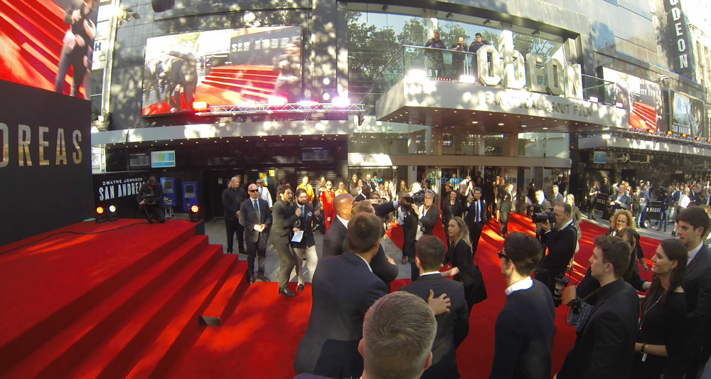 A long line of civilians on the red carpet has been instructed to file rapidly past Dwayne Johnson and get out of the way to make room for the next person. (I forget whether smiling is optional in the selfie world record sense). We're told 75 in 3 minutes is the record.