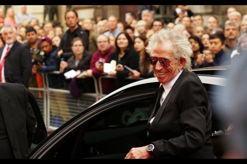 """I'm not signing anything, but hopefully a wide cheesy grin will do?""  Rolling Stone Keith Richards arrives to loud cheers. I last photographed him either at a past GQ Awards or  the premiere of the Rolling Stones film ""Crossfire Hurricane""  back in 2012, and after many fine years of attending, the GQ Academy honoured him with the 'Legend' ""award"" on the night."