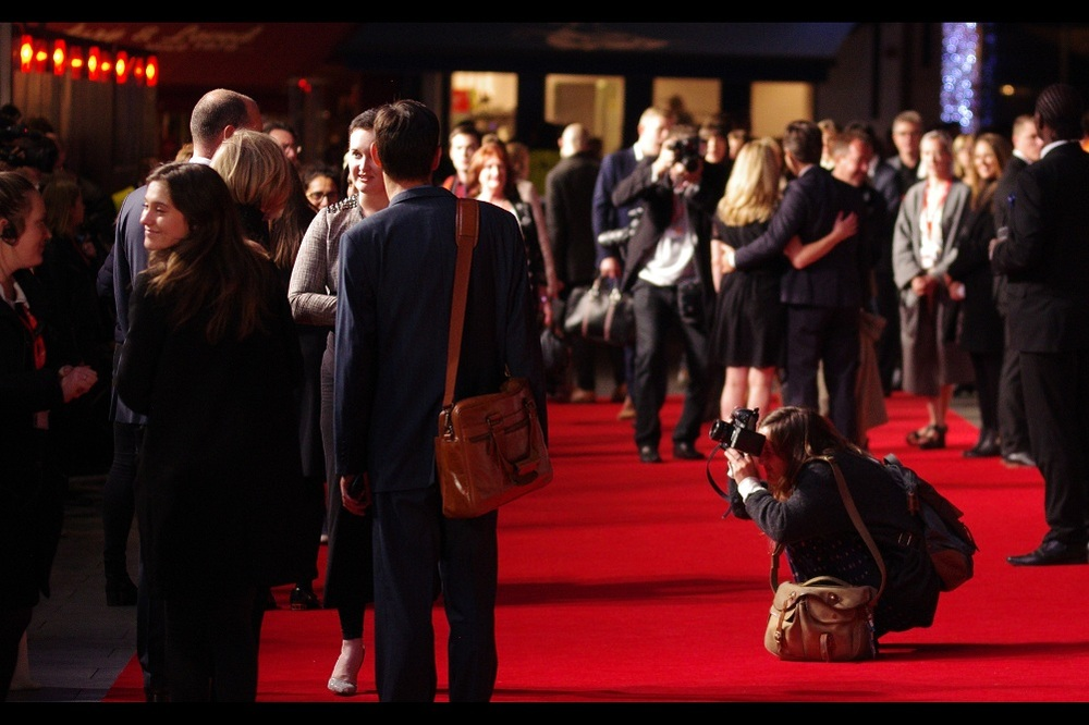 The crowd continues to mill at every possible angle on the carpet, while entourages, attendants, scribes and secretaries hold satchels, .... and even the people on the red carpet (who should be asked to move on into the cinema) are having to get inventive with the unsanctioned photography.