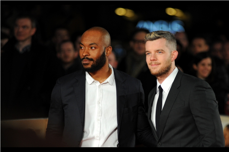 """I don't need a tie to look good... and besides you're all distracted by that squiggle monster in the background anyway, aren't you?""  Arinze Kene joins Russell Tovey in front of the paparazzi cordon, and not since I photographed  Clint Eastwood with neon cappuccino sign above his head  have I done quite so badly with avoiding unfortunate background distractions in a photo."