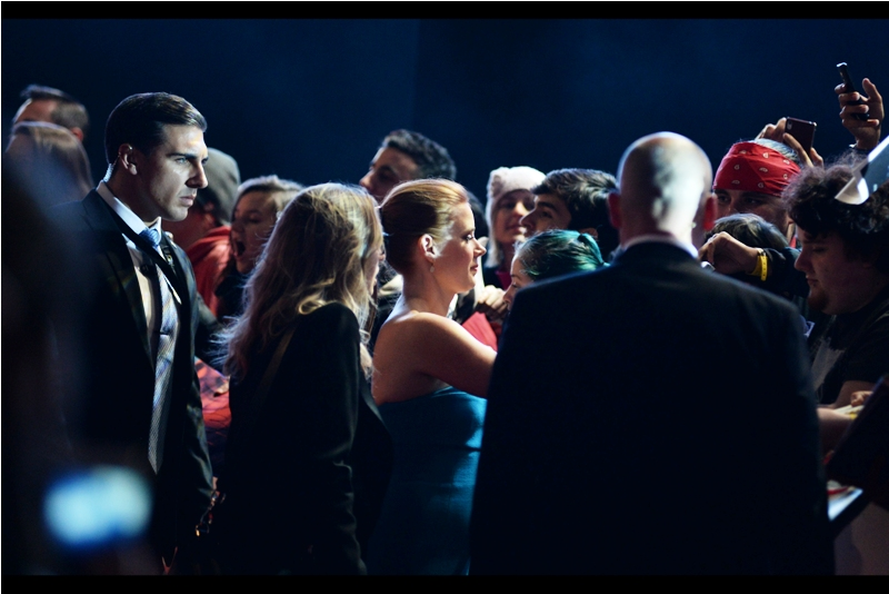 Meanwhile, there's a lot to like in this photo : from the scarily intense look on the face of the security dude on the far left, to the person seeminly using a a 1999-era Nokia phone (which if memory serves didn't actually have a camera) on the far right.. and the lovely Amy Adams in the middle.