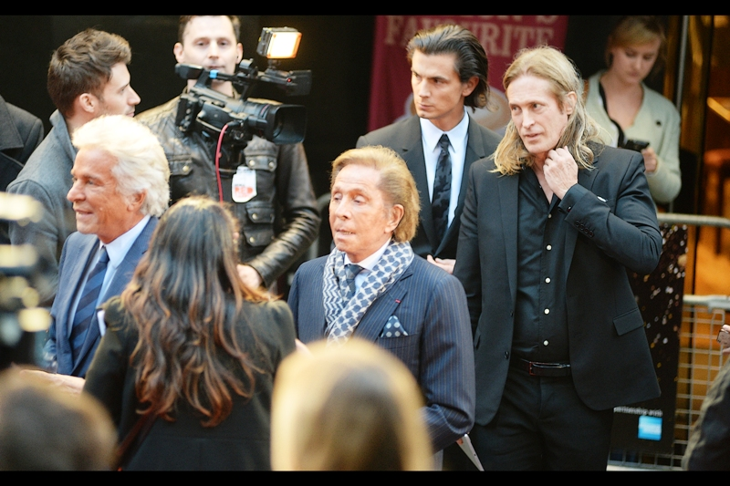 Two of the greatest hairstyles on men and two of the most confusing shades of orange I've seen as skin on men combine in four people. One of whom is fashion designer Valentino, I believe.