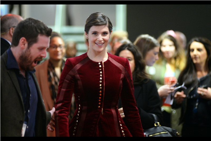 """You like it? My seamstress managed to secure a fantastic discount for purchases above 20 buttons"" - Gemma Arterton has been in such movies (and premieres) as Their Finest (the other premiere) and 100 Streets last year and (say) The Boat That Rocked (which also starred Bill Nighy!)"