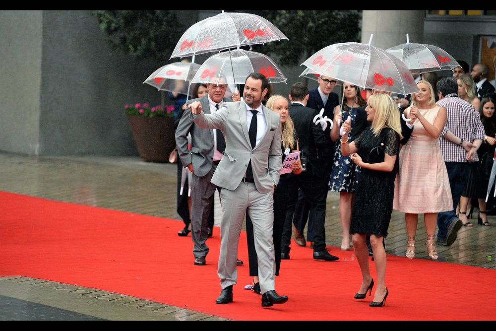 Danny Dyer is too cool for umbreallas. Or waving properly.