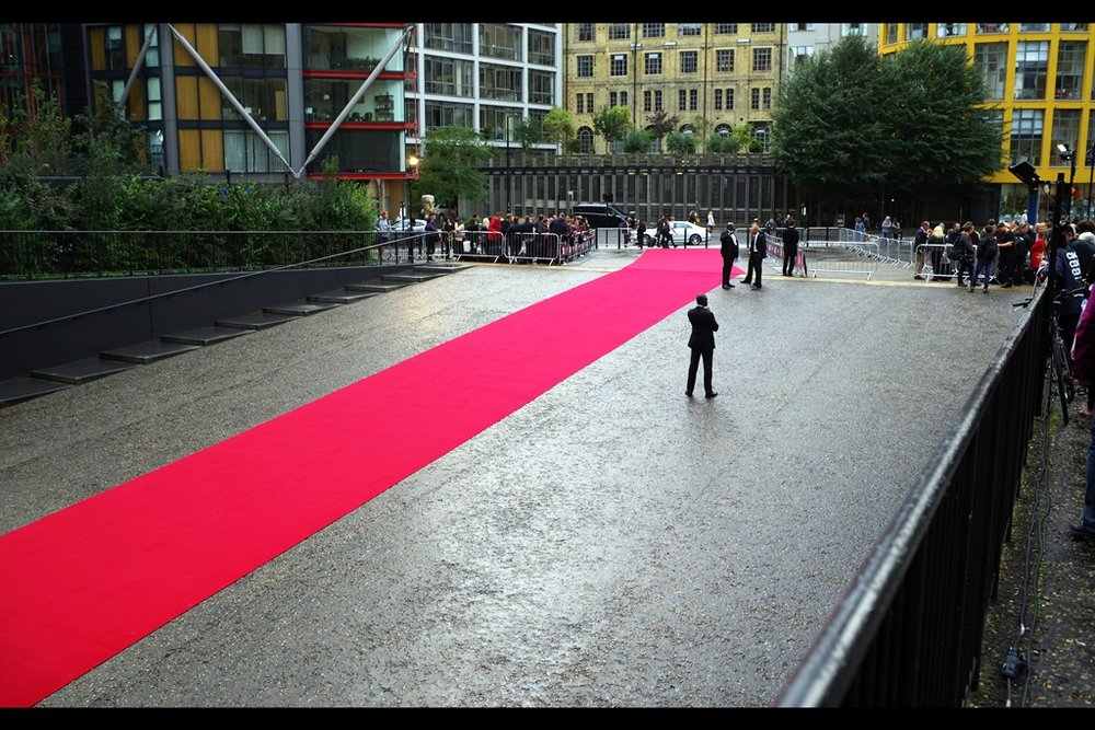 My chosen spot currently overlooks a long, narrow and (for now) well-lit red carpet and approach to the Tate Modern's West entrance. Also, I really hope that one of the guests chooses to rollerblade down that carpet : the slope is pretty great (and I assume the glass doors at the entrance are being left open)