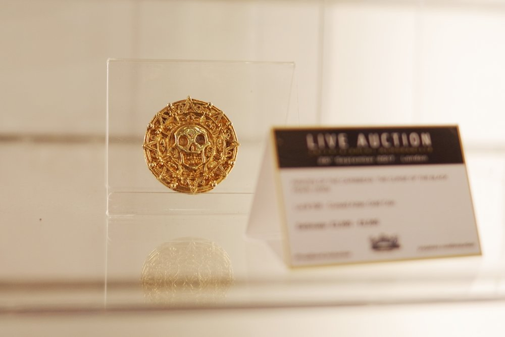 Cursed Aztec Gold Piece from Pirates of the Caribbean. Cursed or not, it's worth more than its weight in gold, I'm guessing.   (Meanwhile, winning bid for Thor's Hammer : £60,000)