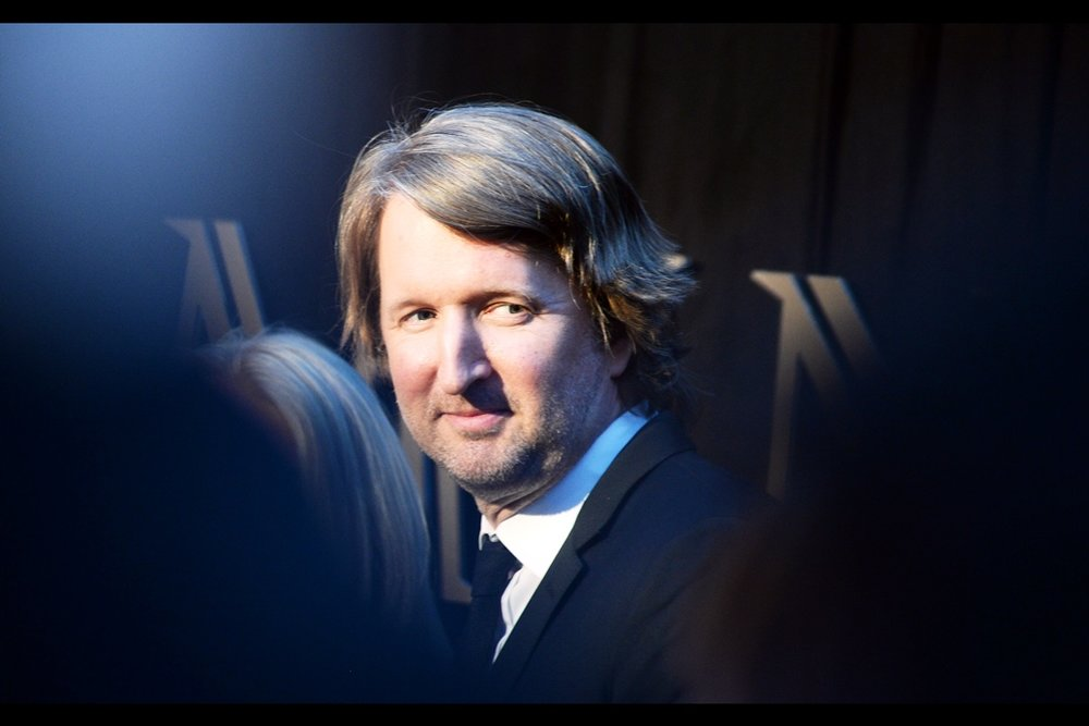 "This is Academy Award Winning director Tom Hooper (for 'The King's Speech' though he also directed   'Les Miserables'  ), photographed though a gap small enough that camels looking at the eye of needles might think  ""I can probably head back to the buffet for another round beforehand""  to."