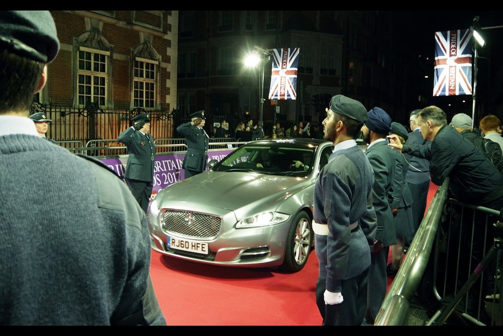 After a suitable last minute sniffer-dog check (during which I had to admit I owned that suspicious looking bag sitting near me, but was not asked to comment on the Pentax over my *other* shoulder), a silver Jaguar rolls up the red carpet. I'd like to say it didn't slow down as it ran over homeless people, but even in the name of questionable humour I shan't.