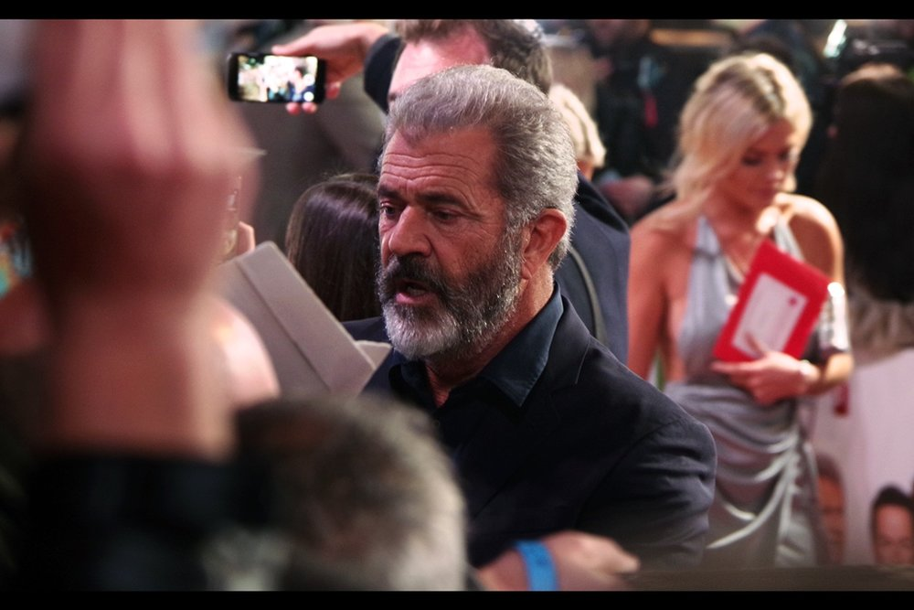 """If your camera has somehow NOT switched focus to the pretty girl behind me, you have my sympathy.""  I'm shooting this photo of Mel Gibson at some distance, which is good because once he gets much closer a wave of autograph dealers will destroy everything in its path, especially my faith in humanity."