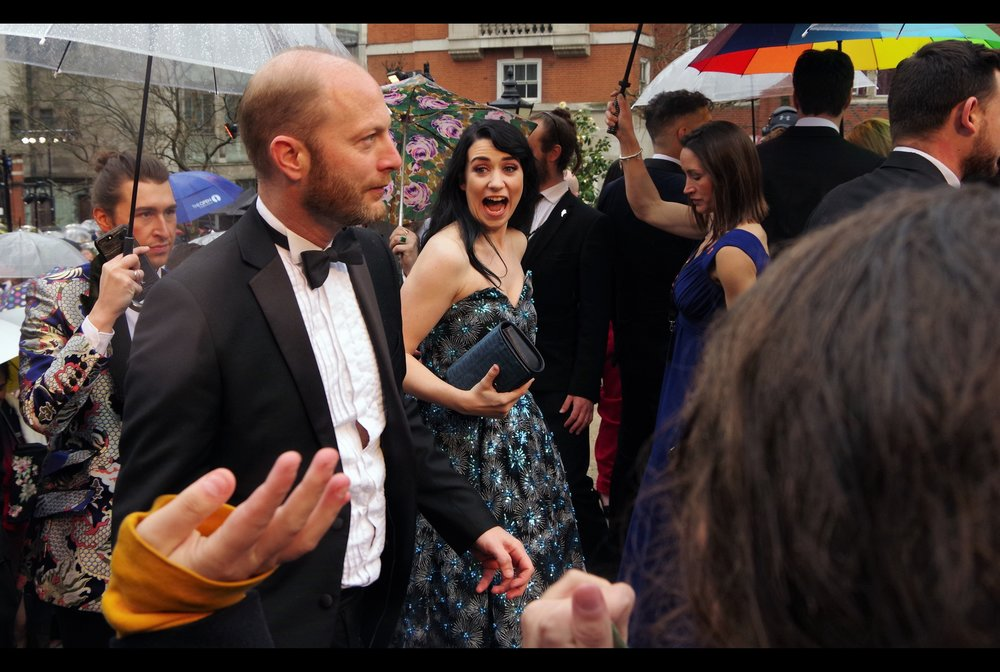 "Lady in Background :   ""OMG! I know this is theatre and I'm meant to be totally understated but that man's hand appears to be FREAKISHLY HUGE!!""  . In other momentous news, Wireimage has finally come through for once... and identified the lady as Danielle Hope."