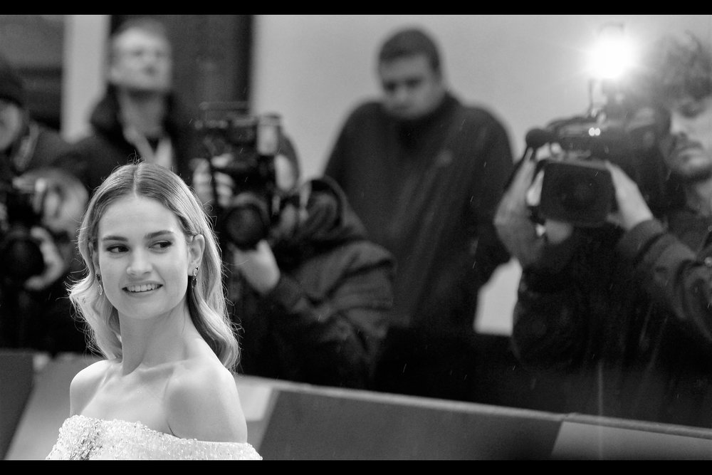 Much as I like Lily James (and I very much do) I'm kind of also taken by the expressions and body language of the people behind her : the glowering shadowy man, and the transfixed cameraman. Alternatively, sure, maybe I'm just using them as pretext to post another photo of Lily James in this journal. Hold your horses, Michiel Huisman fans... he hasn't shown up yet.