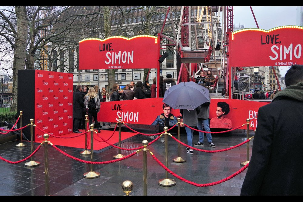 I think might have seen a Dealer Rat walk past the ferris wheel, sniff with disinterest and keep walking... but I can report the presence of a small patch of RED CARPET at this event!! AND rope barriers!! And a posing board!! Hey, don't laugh - this is already a better event than the public elements of the    European Premiere of Black Panther   .